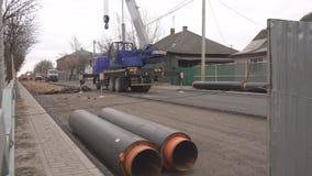 Los trabajos en la ciudad para el reemplazo y desmontar de los tubos para la tubería de calefacción, grúa levantan los nuevos tub almacen de video