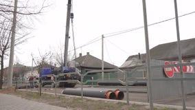 Los trabajos en la ciudad para el reemplazo y desmontar de los tubos para la tubería de calefacción, grúa levantan los nuevos tub almacen de metraje de vídeo