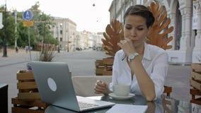 Los trabajos jovenes de la mujer de negocios sobre un ordenador portátil en un café acaban el trabajo metrajes