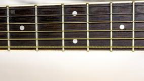 Los trastes de la guitarra con las secuencias corren abajo del cuello Fotos de archivo libres de regalías