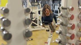 Los trenes de la muchacha en el gimnasio, ella miente en el banco y entrena a los músculos de la parte posterior metrajes
