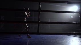 Los trenes del atleta en el anillo oscuro baten sus piernas Silueta Cámara lenta almacen de metraje de vídeo
