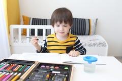 los Tres-años de muchacho están pintando Foto de archivo