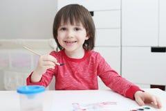 Los tres-años preciosos de niño están pintando con la acuarela en casa Imagen de archivo libre de regalías
