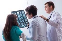 Los tres doctores que discuten resultados de exploración de la imagen de la radiografía Fotos de archivo libres de regalías