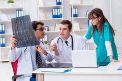 Los tres doctores que discuten resultados de exploración de la imagen de la radiografía Fotos de archivo
