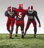 Los tres jugadores de fútbol americano en la acción Fotos de archivo libres de regalías