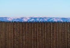 Los troncos de árbol de madera cercan la pared con la montaña de la nieve y la opinión clara del cielo Foto de archivo libre de regalías
