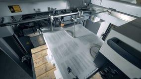 Los trozos de papel impresos están entrando en una máquina del transportador almacen de metraje de vídeo