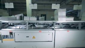 Los trozos de papel impresos se están moviendo a través de una prensa almacen de video