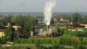 Los tubos de la planta industrial fuman entre árboles y la naturaleza verdes en Alapaevsk metrajes