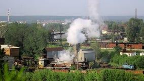 Los tubos de la planta industrial fuman entre árboles y la naturaleza verdes en Alapaevsk almacen de video