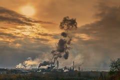 Los tubos de una planta grande fuman en el cielo Imagen de archivo libre de regalías
