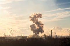 Los tubos de una planta grande fuman en el cielo Imágenes de archivo libres de regalías