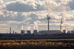 Los tubos de una planta grande fuman en el cielo Fotos de archivo