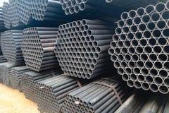Los tubos del metal y de aluminio apilan en el almac?n del cargo para el transporte a la f?brica fotos de archivo