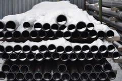 Los tubos plásticos en el almacén acabado de las mercancías se apilan en paquetes en la nieve fotografía de archivo libre de regalías
