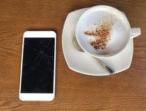 Los tuchscreens agrietados móviles para las comunicaciones son brocken colocado en una tabla de madera y las tazas de café en c fotos de archivo