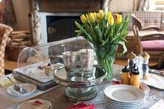 Los tulipanes amarillos de la cuchillería en un florero desayunan en el h foto de archivo