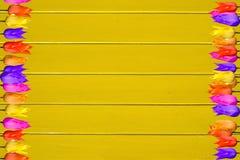 Los tulipanes coloridos en amarillo brillante pintaron el fondo de madera foto de archivo