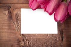 Los tulipanes florecen con la tarjeta de felicitación sobre la tabla de madera Imágenes de archivo libres de regalías