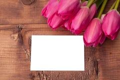 Los tulipanes florecen con la tarjeta de felicitación sobre la tabla de madera Fotografía de archivo libre de regalías