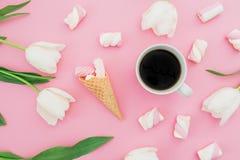 Los tulipanes florecen con la taza de café, de melcochas y de cono de la galleta en fondo del rosa en colores pastel Concepto del fotos de archivo