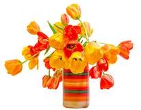 Los tulipanes rojos, amarillos y anaranjados florecen en el florero rústico coloreado, arreglo floral, cierre para arriba, fondo  Fotos de archivo libres de regalías