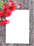 Los tulipanes rojos descolorados en el roble broncean la tabla con la hoja blanca del pape Imagen de archivo libre de regalías