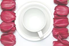 Los tulipanes rojos mienten en un fondo blanco cerca de la taza del café con leche, que se coloca en un platillo blanco imagen de archivo