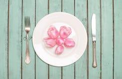 Los tulipanes rosados dirigen sobre la placa con los cubiertos en la madera elegante lamentable Imagen de archivo