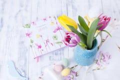 Los tulipanes son rosados y amarillos en un florero en la tabla Fondo blanco Espacio libre para el texto o una postal Semana Sant Imagen de archivo