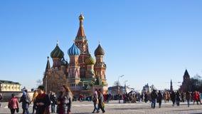 Los turistas acercan a la catedral de la albahaca del St. en Plaza Roja
