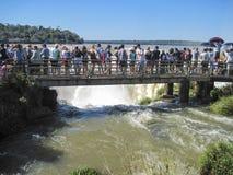 Los turistas admiran las caídas de Iguacu (Iguazu) en una frontera del Brasil y foto de archivo libre de regalías