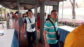 Los turistas asiáticos pasan a través del marco del detector de metales en el camino al templo de Emerald Buddha almacen de video