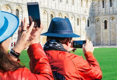 Los turistas asiáticos toman imágenes de la torre inclinada de Pisa Imágenes de archivo libres de regalías