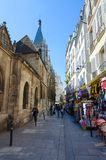 Los turistas caminan a lo largo de Rue Saint-Severen estrecha cerca de la iglesia del santo Severin y de tiendas de souvenirs en  fotografía de archivo libre de regalías