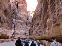 Los turistas caminan a lo largo del barranco de color rojo oscuro en la capital antigua de Jordania, Petra imágenes de archivo libres de regalías