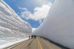 Los turistas caminan a lo largo del pasillo de la nieve en Tateyama Kurobe Rou alpino Imagen de archivo libre de regalías