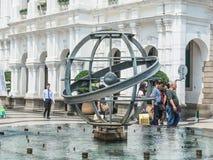 Los turistas caminan paso la estatua del globo del metal en la fuente en el cuadrado de Senado en Macao, China Fotos de archivo