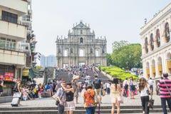 Los turistas caminan paso y toman las fotos en las ruinas del ` s de San Pablo en día soleado en Macao, China Foto de archivo