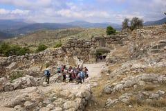 Los turistas caminan a través de la puerta del ` s del león de la ciudadela de Mycenae Fotografía de archivo