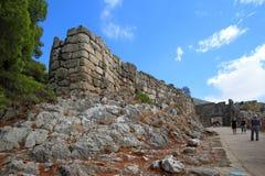 Los turistas caminan a través de la puerta del ` s del león de la ciudadela de Mycenae Fotos de archivo