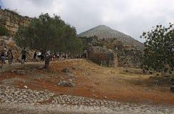 Los turistas caminan a través de la puerta del ` s del león de la ciudadela de Mycenae Fotografía de archivo libre de regalías