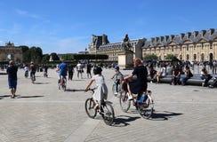 Los turistas completan un ciclo en el museo del Louvre en París, Francia fotografía de archivo