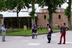 Los turistas con las cámaras, los teléfonos móviles y los palillos del selfie están llevando las fotos cerca el palacio de Topkap foto de archivo libre de regalías