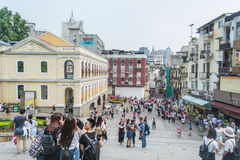 Los turistas dan une vuelta y toman las fotos delante de las ruinas del ` s de San Pablo en Macao Imágenes de archivo libres de regalías