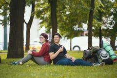 Los turistas de los adolescentes con las mochilas están comiendo el helado en el parque Fotos de archivo libres de regalías