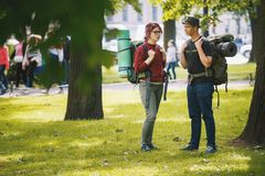 Los turistas de los adolescentes con las mochilas tienen conversación en el parque en el mediodía del verano Fotos de archivo libres de regalías