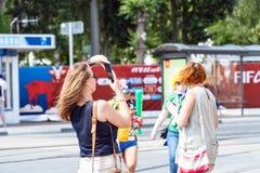 Los turistas de las muchachas toman imágenes en la calle durante el mundial 2018 Foto de archivo